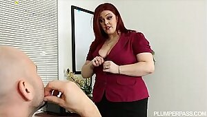 Busty redhead feasting on big tit boss