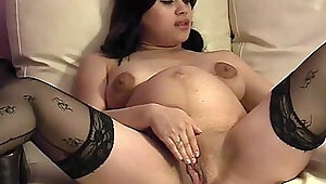 Pregnant babe toys her creamy pussy